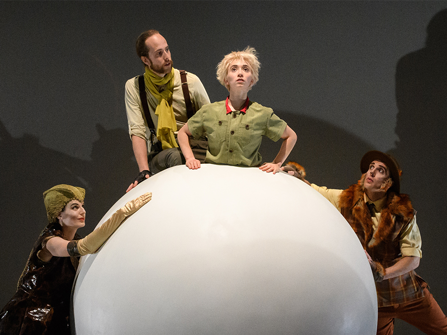 a picture from the play little Prince leans on a planet while 3 other characters surround him