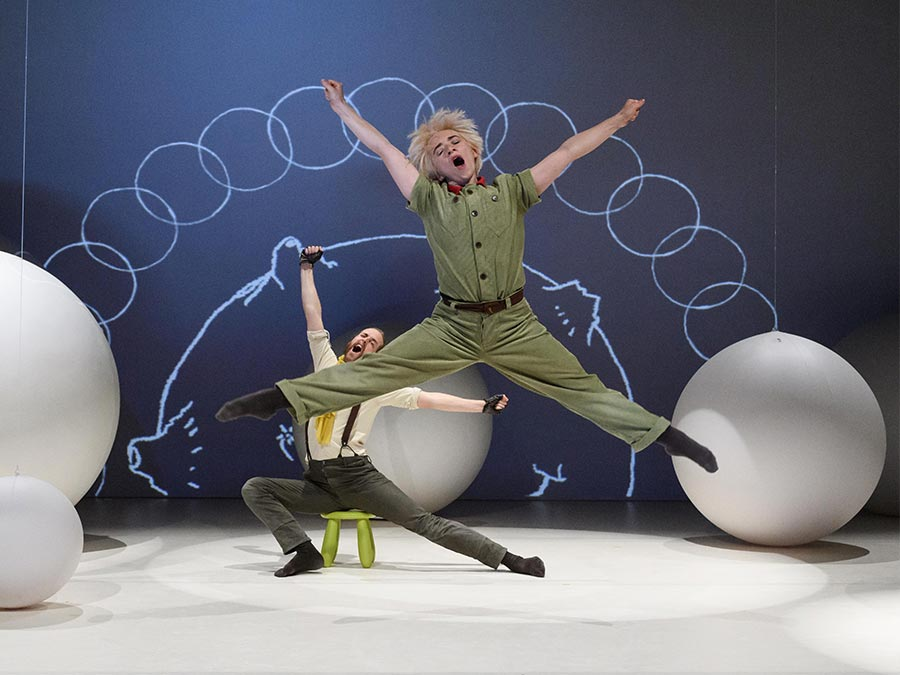 Protein's The Little Prince leaps in the air with legs and arms stretched out wide. He is yawning and wearing a khaki green, buttoned-up suit. In the background, the pilot is sitting on a stool yawning and stretching.