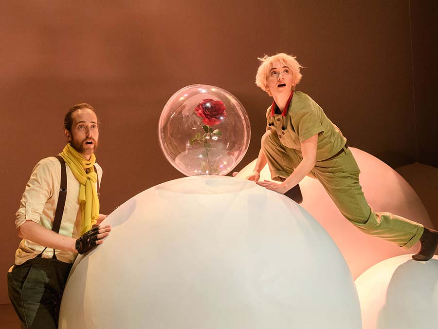 The Little Prince lunges between two white balls. He is gazing upwards with his mouth open. He is wearing a khaki green, buttoned-up suit. In the center a single rose has a plastic bubble around it and the pilot is stood on the ground to the left.