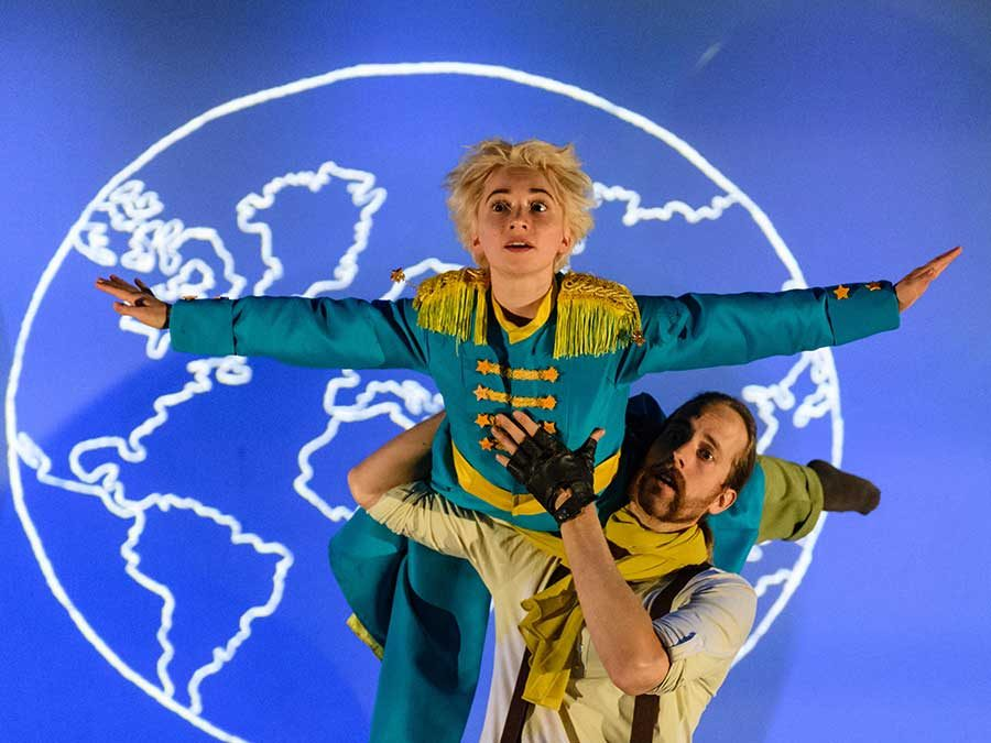 The Pilot holds The Little Prince on his shoulder. The Little Prince imitates a plane and has both his arms out to the side. He wears a long blue coat with gold details. In the back a white drawing of earth is projected on a light blue background.