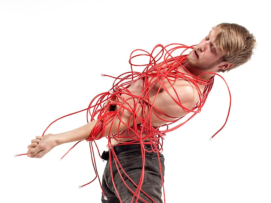 a shirtless man with his torso and hands bound by a red string