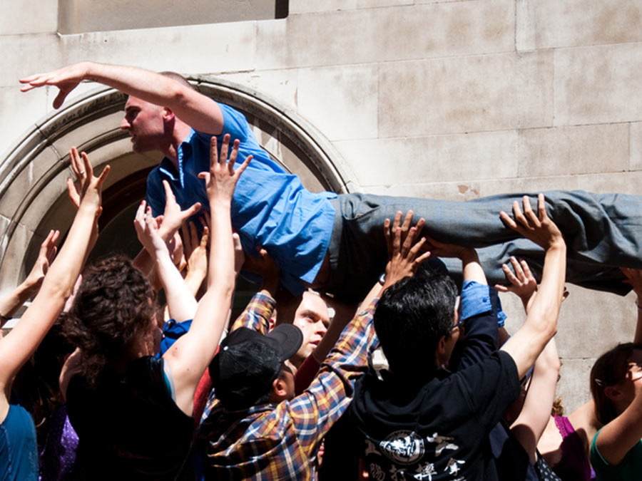 a bunch of people lifting up a man wearing a blue shirt