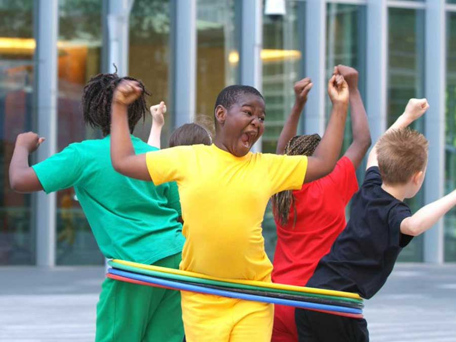Kids in bright coloured clothing are standing inside a hula hoop
