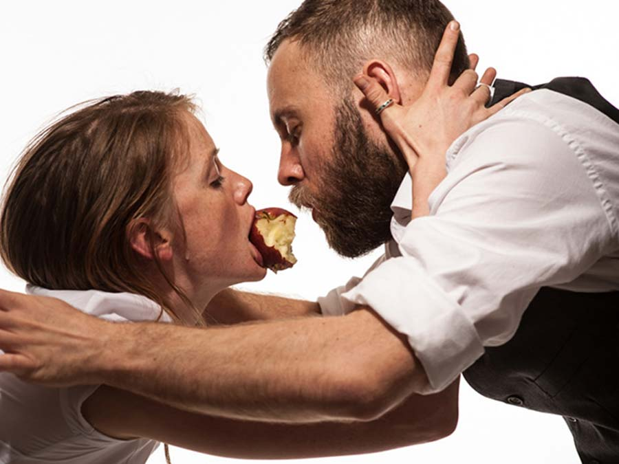 a man and a woman embracing each other, with their faces really close the woman has a half eaten apple in her mouth