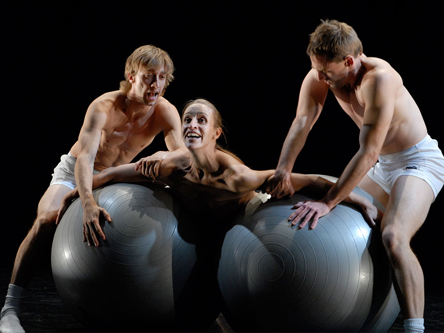 A woman with her arms spread is laying on two grey bouncy balls, each ball is being held in place by a man
