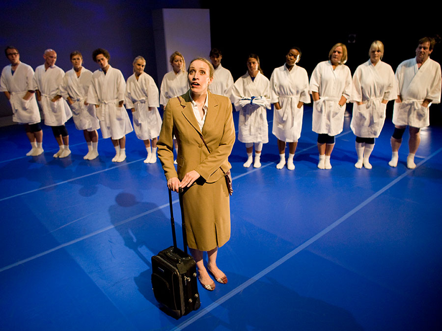 a woman dressed in a mustered coat with a suitcase standing in front of a line of people dress all in white