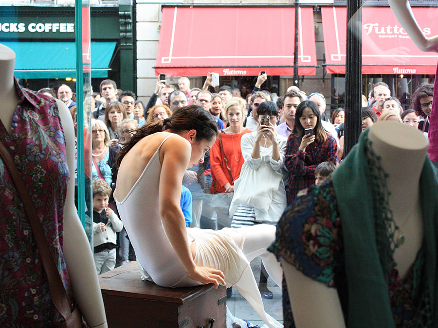 a woman bending her back sitting on a box in a shop window, while people on the street are watching