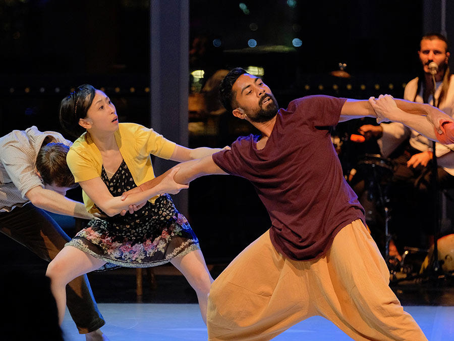 A stage shot from Protein's Border Tales. A dancer in a burgundy t-shirt and beige balloon trousers is being pulled in opposite directions. There is a woman wearing a black flowery dress and a yellow cardigan pulling him towards the back of the stage.