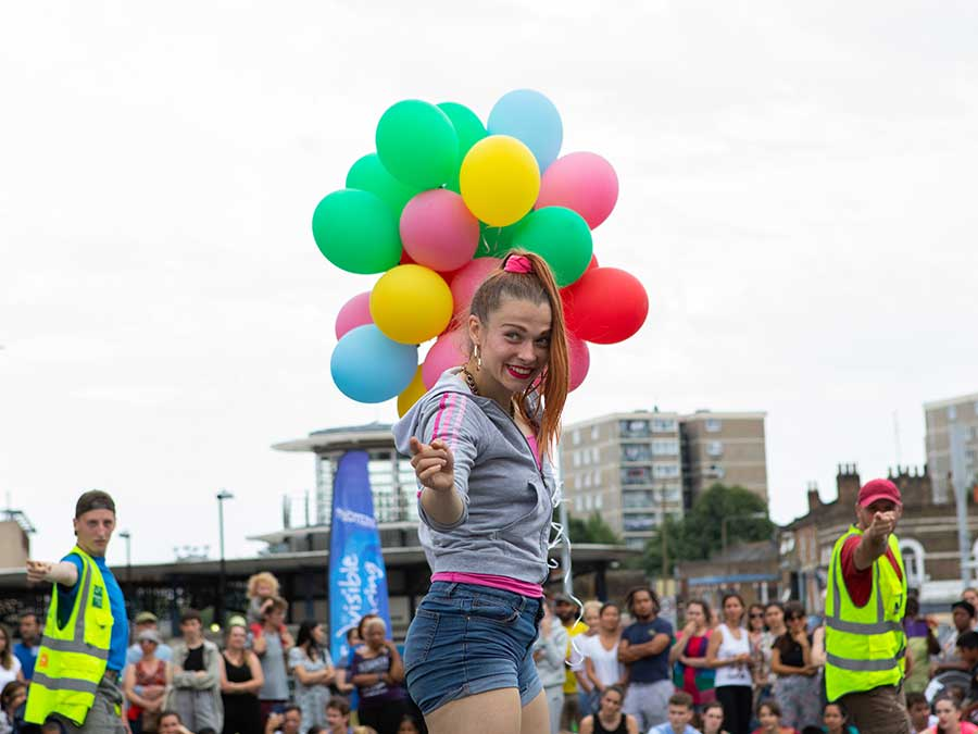 a woman dressed in sporty clothing is pointing at the camera, with a bunch of colourful balloons behind her