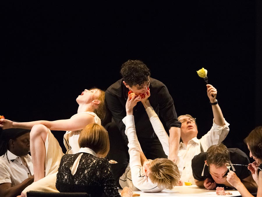 eight dancers laying on the stage, in the middle a man hovering over a woman with her arms up pushing an apple into his mouth