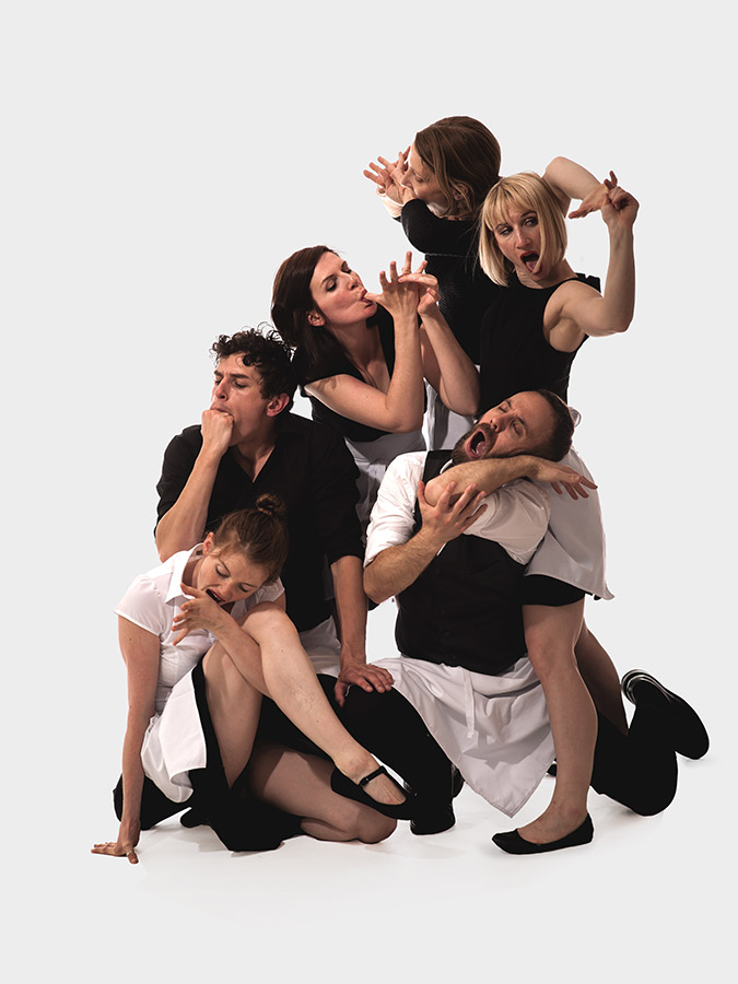 A group of people in waiter's uniforms with white aprons huddle in a group. They try and their own fingers, fists and elbows.