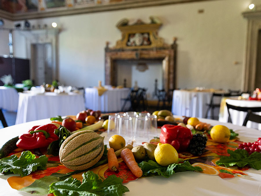 A round table with a white cloth has a variety of fruits and vegetables laid across it. In the middle there are some clear glasses
