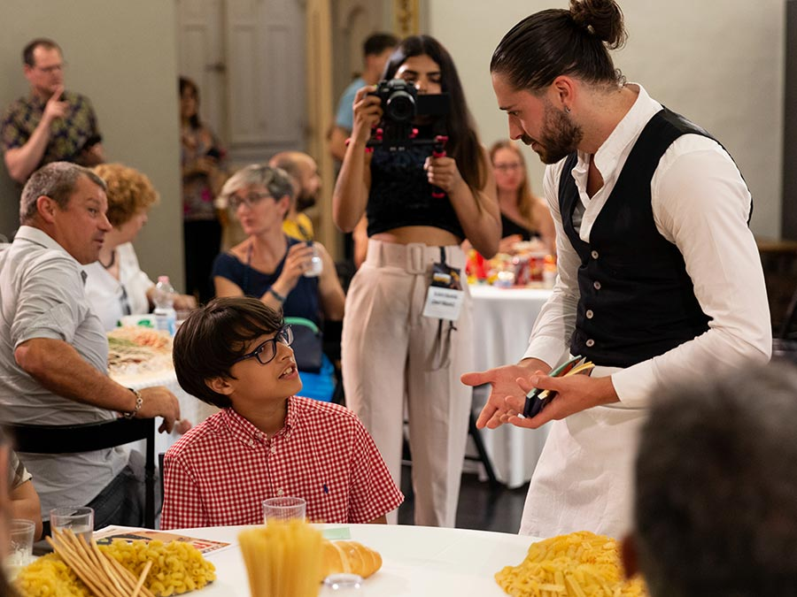 A young boy in a white and red checkered shirt sits at a round table. A performer dressed as a waiter from Protein's FOOD talks to the boy. In the background there are more guests at tables and a female photographer.