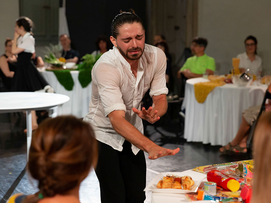 A performer from Protein's FOOD has a look of disgust on his face. He is hunched over a table with both his arms out in front of him. Around his are other tables with guests sat at them.