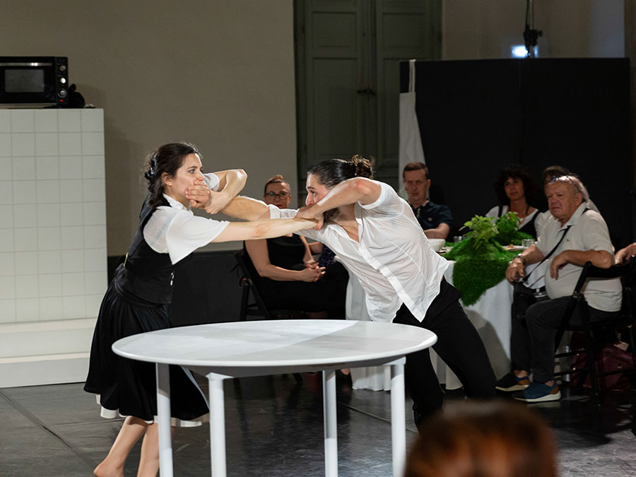 A male performer from Protein's FOOD is dressed in a white shirt and black suit trousers. He has his left hand over a female performers mouth. She wears a black skirt, a white blouse and black waistcoat. Her hand is also over the other performers mouth. They use their other hand to try pull the hands away from their mouths. They struggle over a white, round table.