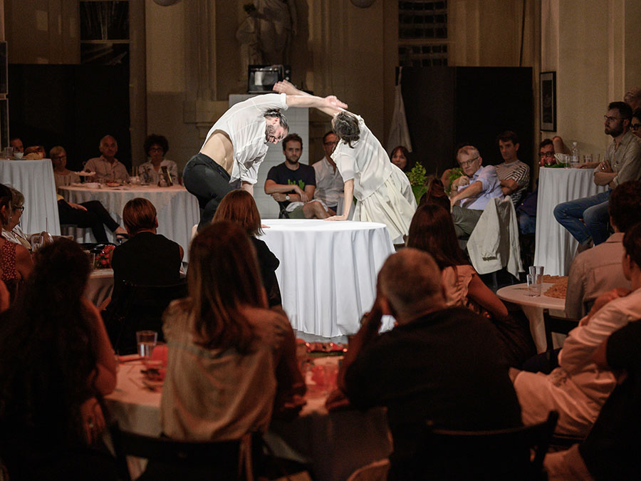 A scene from Protein's food. Guests sat at round tables with white table cloths look towards the center where two performers lean with their right arms over their heads to opposite sides of the table.