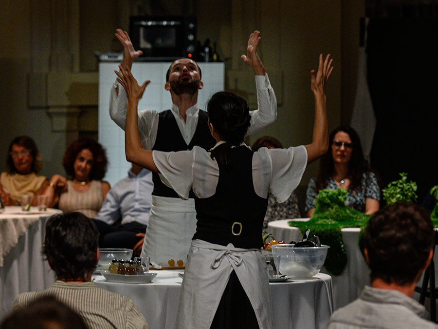 Two performers dressed as waiters from Protein's FOOD stand at opposite sides of a round table. There are various kitchen utensils on it. They have both arms raised up to the sky in an L shape.