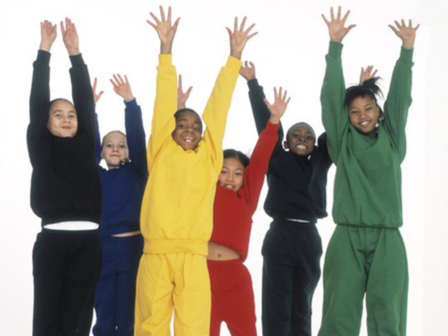 Six children dressed in colourful clothing with their hands up.