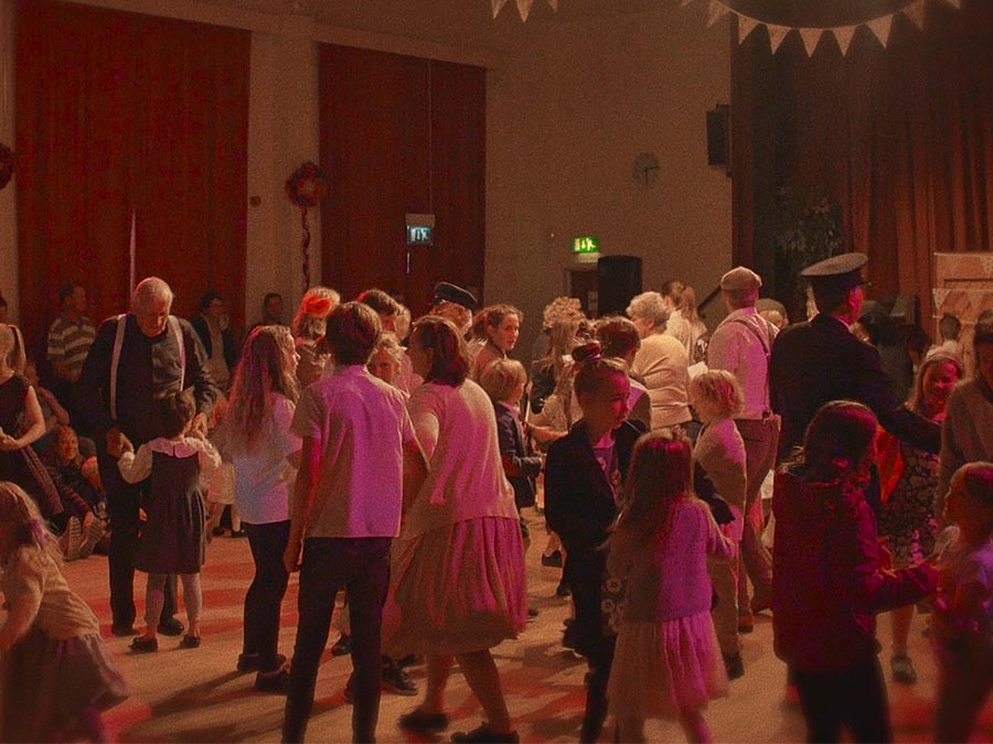 a large room, with party decoration a lot of children and a few adults standing in it