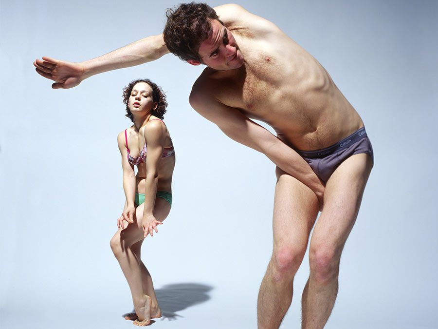 Two people in their underwear standing in front of a white background. A woman in the back is crouching with her hands in front of her body, the man in the front is stretching his left hand over his head.