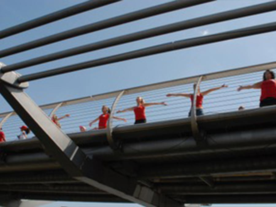 A line of people dressed in red shirts doing jumping jacks on a bridge.