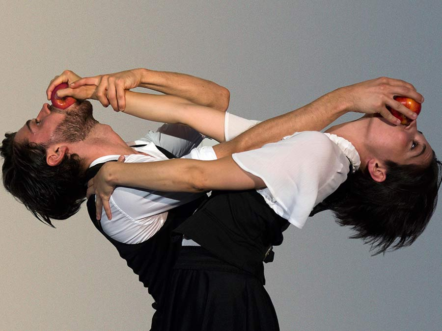 A male and female performer from Protein's FOOD lean their heads back whilst arching their backs. Their both dressed in white shirts and black waistcoats. The male holds a red apple in the females mouth, she also holds a red apple in his mouth as she grabs his right shoulder with her left hand.