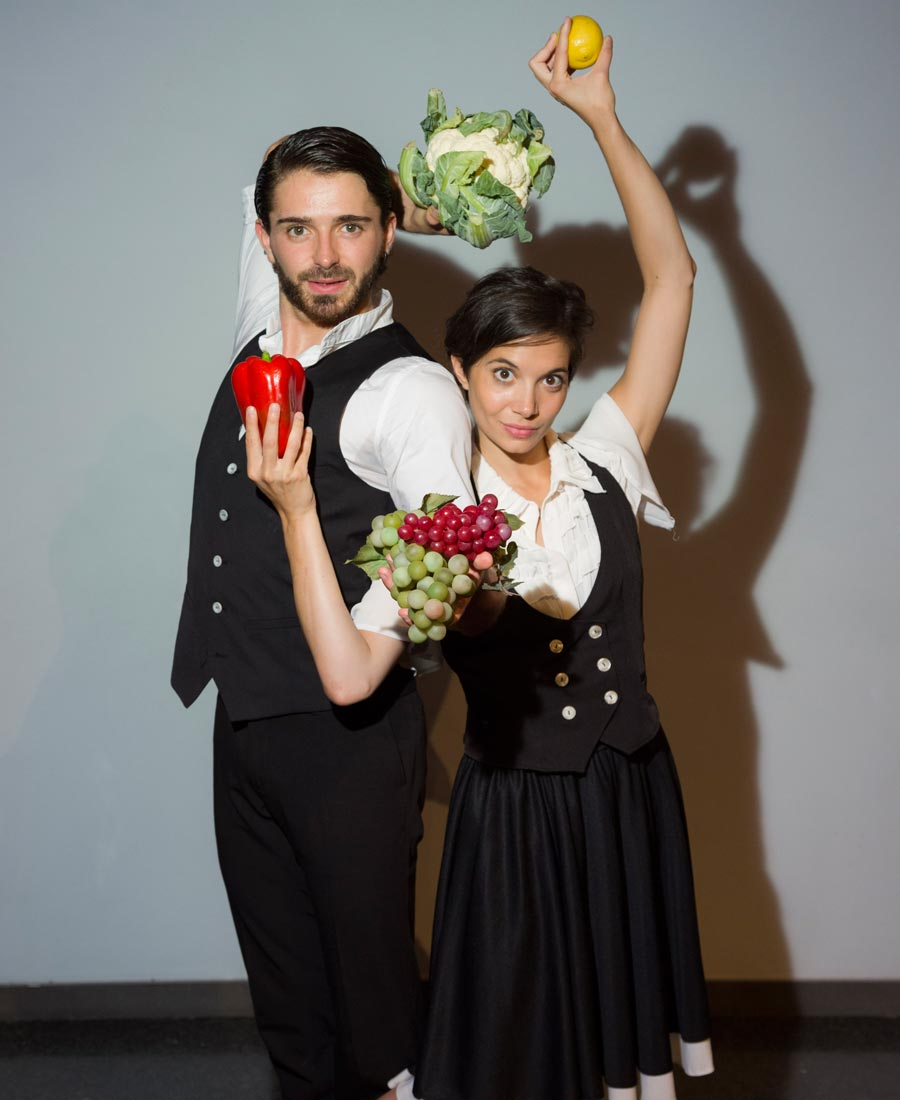 A male performer from Protein's food holds a cauliflower behind his head with his left hand. He holds a bunch or green and red grapes in his right hand which is stretched forward. Next to him is a female performer. She holds a lemon in her right arm raised above her head. She holds a large red pepper in her left hand that goes under his right. Their silhouettes can be seen on the white background.